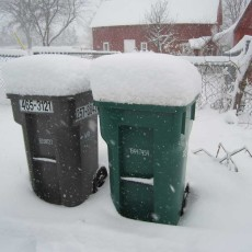 A foot of snow atop a garbage bin and a recycling bin.